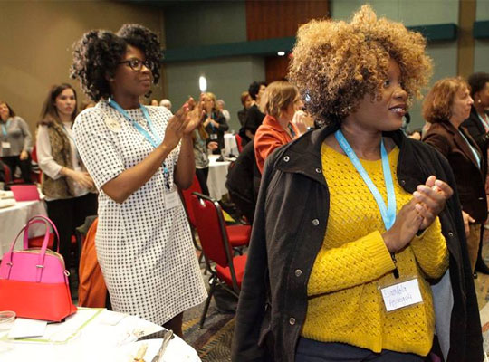 Two female summit participants clapping