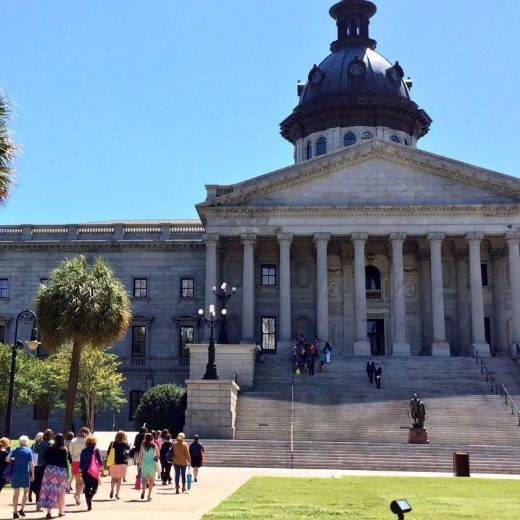 SC State House with people walking up to it on sidewalk