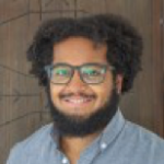 Headshot of DJ Polite, African american man with beard and glasses in blue shirt smiling toward camera