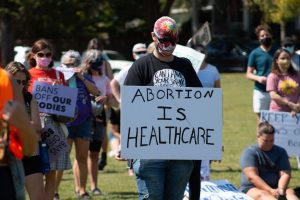 Person in black tshirt holding a sign that reads abortion is healthcare
